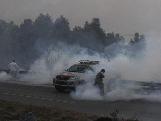A supporter of Imran Khan's Pakistan Tehreek-e-Insaf party throws a teargas shell towards police during a clash in Hazro, Pakistan, on Monday. Pakistani police launched a nationwide crackdown overnight, arresting at least 1,500 supporters of Khan ahead of a planned  lockdown of Islamabad.