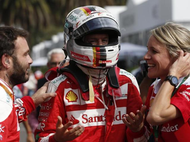 Ferrari team members confirm to Ferrari driver Sebastian Vettel, of Germany, that he has won third place during the Formula One Mexico Grand Prix.