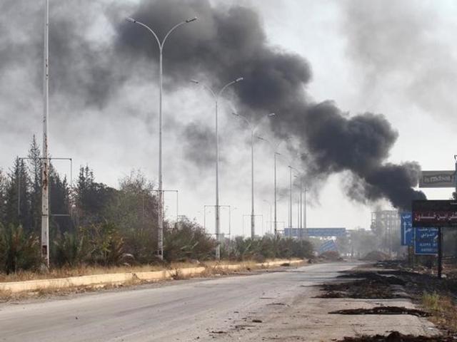Smoke rises near a damaged road in Dahiyet al-Assad, west Aleppo city, Syria.