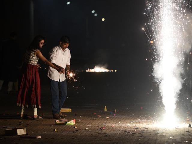 Children burst fire-crackers during Diwali festival celebration on Sunday, in Gurgaon