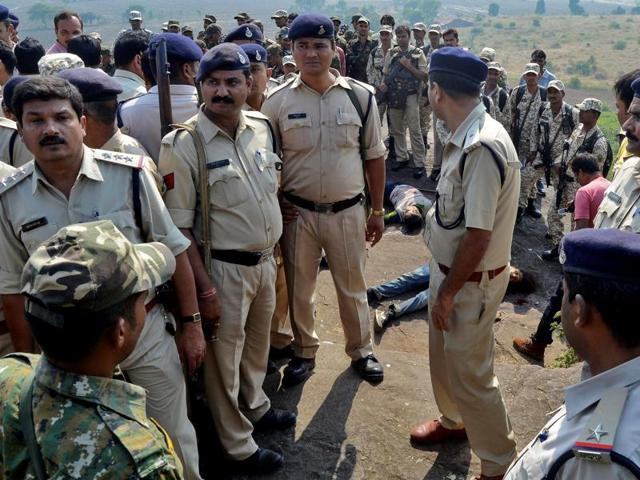 Police officers and Special Task Force soldiers stand beside dead bodies of the suspected members of the banned Students Islamic Movement of India (SIMI), who escaped the high security jail in Bhopal, and later got killed in an encounter.