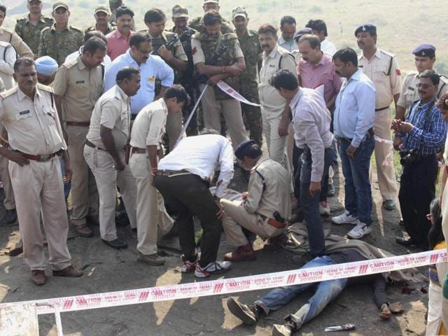 Police personnel at the encounter site at the hillocks of Acharpura village after the STF killed 8 suspected SIMI operatives in Bhopal.(PTI Photo)
