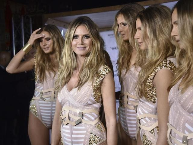 Model and television personality Heidi Klum, center, talks to the media with
