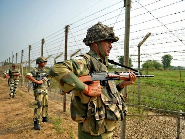 Border Security Force (BSF) soldiers take up positions at an outpost along a fence at the India-Pakistan border in RS Pura sector of Jammu.
