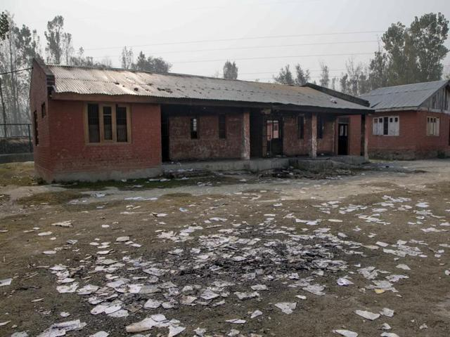 Destroyed books sit in the yard of a partially burned government high school in Goripora, outskirts of Srinagar.