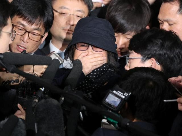 Choi Soon-sil (center wearing a hat) a cult leader's daughter with a decades-long connection to President Park Geun-hye, is questioned by media upon her arrival at the Seoul Central District Prosecutors' Office in Seoul.