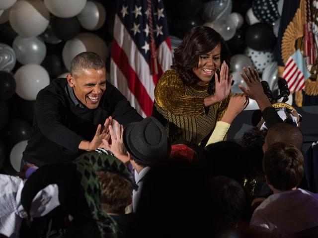 US President Barack Obama and First Lady Michelle Obama high-five children after they performed Michael Jackson'n Thriller in the East Room at the White House during a Halloween event in Washington, DC, on October 31, 2016. / AFP PHOTO / NICHOLAS KAMM