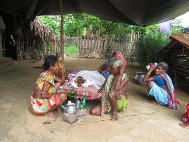 Relatives of a tribal kid who died of Encephalitis grieving near her body at a village in Malkangiri.