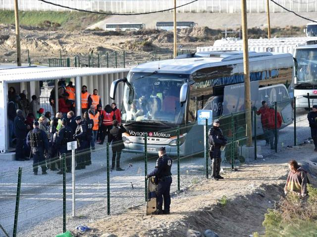 Police officers and volunteers stand near a bus as unaccompanied migrant minors from the demolished