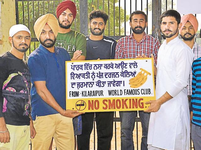 Members of the Kila Raipur sports club with the board that explains their 'bananas' rule.