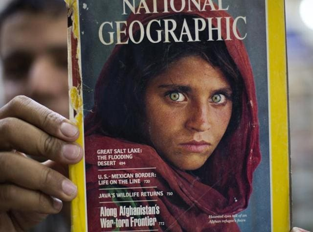 A book shop owner shows a copy of a magazine with the photograph of Afghan refugee woman Sharbat Gulla, from his rare collection in Islamabad, Pakistan.