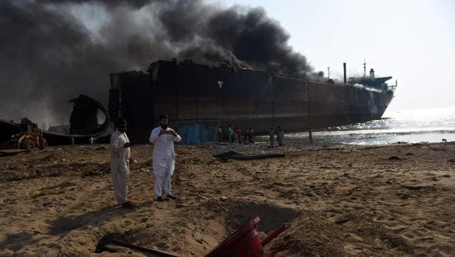A Pakistani man takes pictures in front of a burning ship after a gas cylinder explosion at the Gadani shipbreaking yard, some 50 kilometres (30 miles) west of Karachi on November 1, 2016.