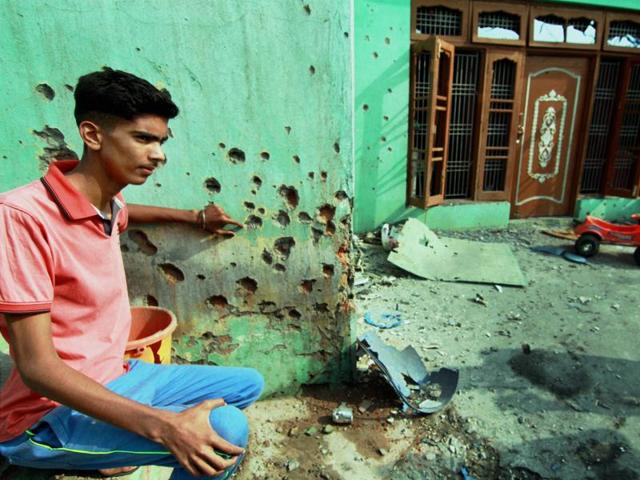 A villager showing the wall of a building damaged by alleged shelling from the Pakistani side at Rangoor camp in Ramgarh sector.