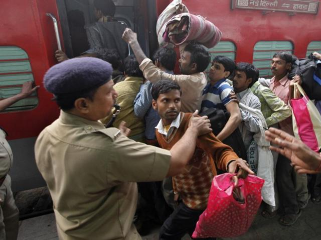 Railway Police manage crowds attempting to board the Bihar Sampark Kranti train during the Chhath festival in November 2013 in New Delhi. Migrant workers who travel in scores are soft targets for thieves during this time.