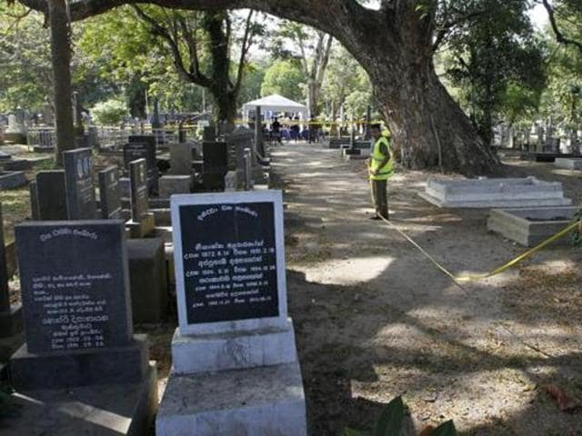 Sri Lankan crime investigating police officers prepare to exhume the remains of murdered newspaper editor Lasantha Wickrematunge at a cemetery in Colombo, Sri Lanka, Tuesday, Sept. 27, 2016, following a court order for a fresh investigation. Wickrematunge, editor of the Sunday Leader newspaper, was killed while driving to work in January 2009.