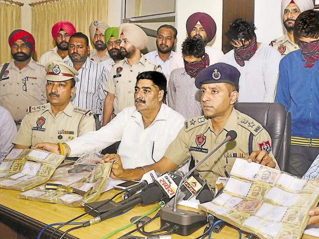 DCP Gagan Ajit Singh showing the recovered money during a press conference at Police Lines in Amritsar on Wednesday.