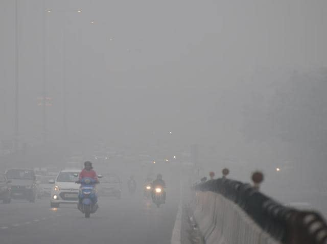Vehicles play on the Delhi-Gurgaon Expressway on November 2 in the decreased visibility caused by smog.