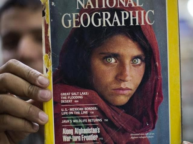 In this file photo, the owner of a book shop shows a copy of a magazine with the photograph of Afghan refugee woman Sharbat Gulla, from his rare collection in Islamabad, Pakistan.