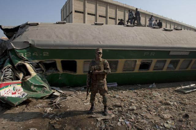 People look for victims in the wreckage of the trains in Karachi, Pakistan.