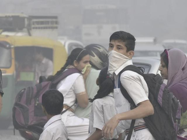School children cover their face with handkerchiefs as smog continues to cover the skyline in New Delhi for the third consecutive day on Friday.
