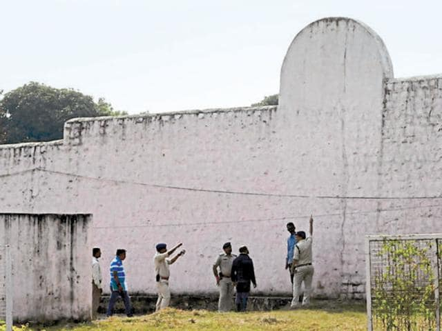 Investigating officers inspecting the spot from where the 8 alleged SIMI activists escaped after climbing the 28-feet wall with the help of bedsheets early on Monday morning.(Mujeeb Faruqui/HT PHOTO)