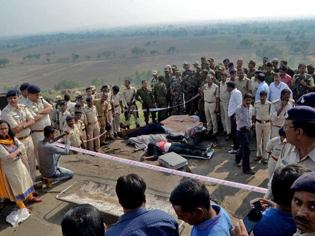 Police officers and Special Task Force soldiers stand beside bodies of the eight SIMI operative who escaped the high security jail in Bhopal on October 31, 2016. The men were killed in an encounter at the Acharpura village on the outskirts of Bhopal.
