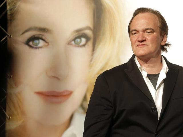 Director Quentin Tarantino poses in front of a picture of French actress Catherine Deneuve as he arrives at the opening ceremony of the 8th Lumiere Festival, in Lyon, central France.
