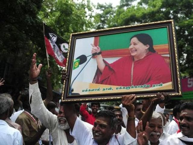 Members of the All India Anna Dravida Munnetra Kazhagam(AIADMK) party carry placards with the image of AIADMK leader Jayalalithaa.