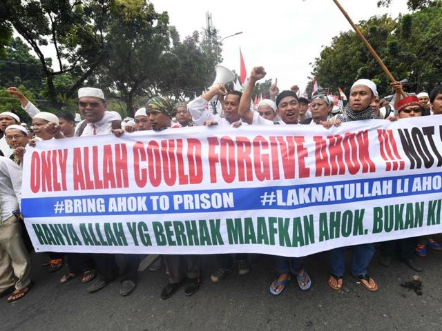 Muslim protesters gather with a banner calling for the arrest of Jakarta's ethnic Chinese and Christian Governor Basuki Tjahaja Purnama on blasphemy.
