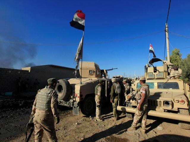 Members of Iraqi security forces sit on military vehicles during a battle with Islamic State militants in southeast of Mosul, Iraq.