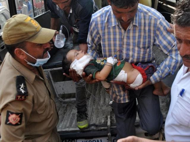 Indian volunteers and officials carry fourteen-month-old Pari into The Government Medical College Hospital in Jammu on November 1, 2016, after she was injured in cross-border shelling in Kashmir.