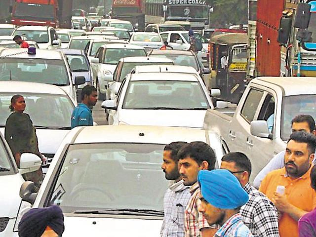 The blocked Ludhiana-Ferozepur highway; and (right) taxi drivers protesting after a cabbie was assaulted by a commuter in Ludhiana on Friday.