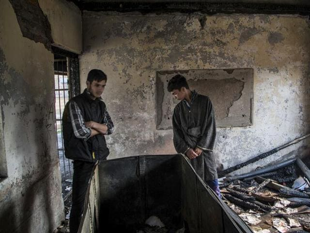 A Kashmiri student looks out of a window of a partially burnt government high school in Goripora, on the outskirts of Srinagar on November 2, 2016.