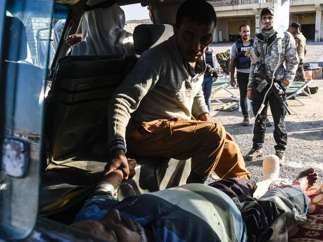 An injured Iraqi man lies inside a van on November 4, 2016, near the village of Gogjali, Iraq.
