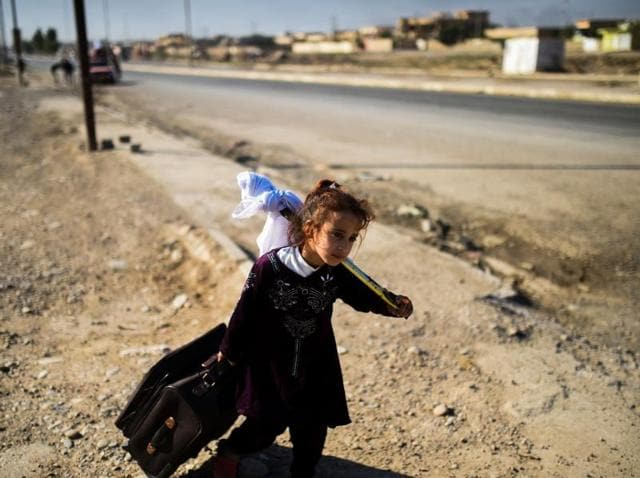 Iraqi families drive through the village of Gogjali, on the eastern edge of Mosul, on November 4, 2016, as they flee the violence due to the ongoing operation by Iraqi forces to retake the city from the Islamic State.