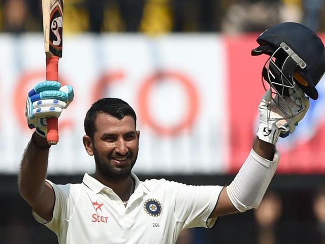 Cheteshwar Pujara raises his bat after completing his half-century against New Zealand.