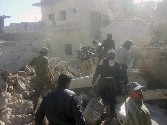 This photo provided by the Syrian Civil Defense White Helmets, which has been authenticated based on its contents and other AP reporting, shows Civil Defense workers and Syrian citizens inspecting damaged buildings after airstrikes hit in Darat Izza town, in rural western Aleppo province, Syria.