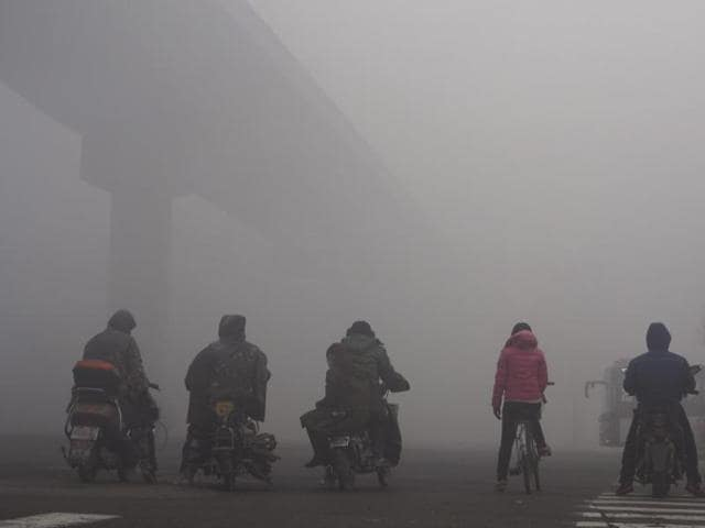 Residents on their bicycles and electric bikes wait for the traffic at an intersection amid heavy smog in Shijiazhuang, Hebei province, China, December 10, 2015.