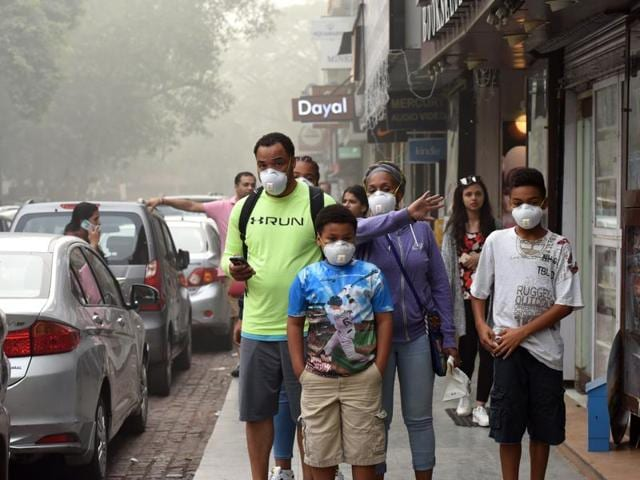 People wear masks as air pollution sparks fears of health hazards, at Khan Market in New Delhi.