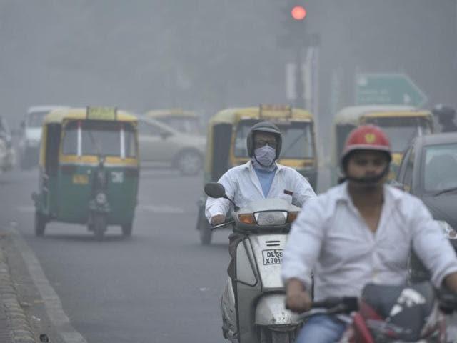 People wear air masks as smog covers capital's skyline.
