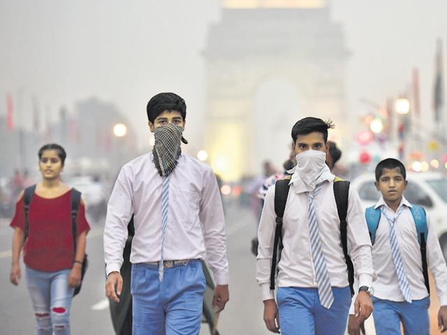 School students cover their face with a handkerchief to avoid thick smog in Delhi.