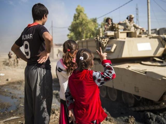 Iraqi children, one flashing the sign of victory, greet Iraqi army's soldiers from the 9th armoured division in the area of Ali Rash, adjacent to the eastern Al-Intissar neighbourhood of Mosul, on November 6, 2016, during a military operation to retake the main hub city from the Islamic State (IS) group jihadists.