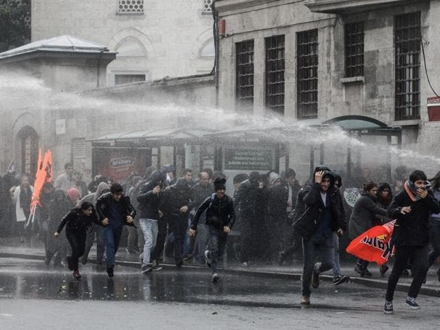 People run as Turkish riot police uses water cannon to disperse protesters on November 5, 2016 during a demonstration in Istanbul. Turkey jailed on November 4 the two leaders of the country's main pro-Kurdish party and several other MPs, in an unprecedented crackdown as a bombing killed nine in the Kurdish-dominated southeast.
