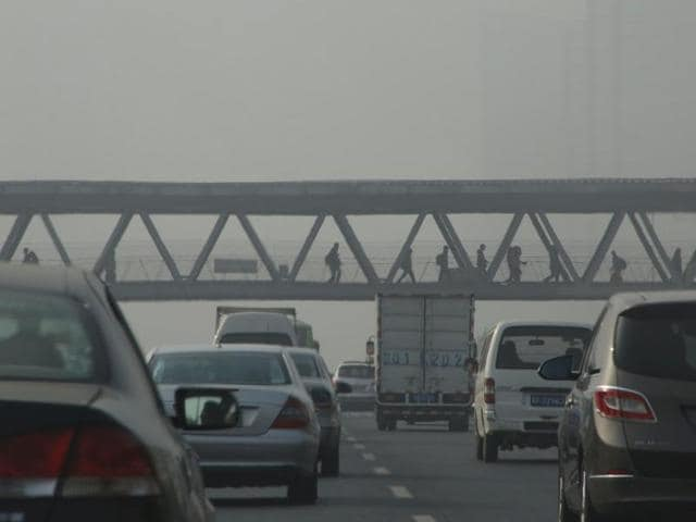 Vehicles drive past a pedestrian bridge in the haze of Beijing, China.