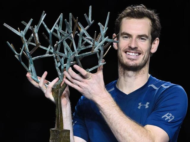 Britain's Andy Murray poses with his trophy on the podium after winning the final tennis match against USA's John Isner.
