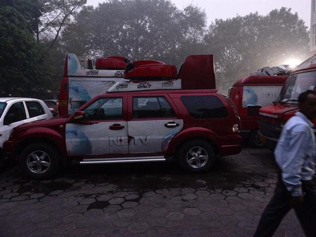 An Indian man walks in a parking lot of Indian news channel NDTV in New Delhi.