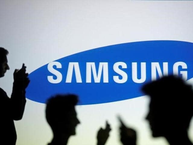 People are silhouetted as they pose with mobile devices in front of a screen projected with a Samsung logo.