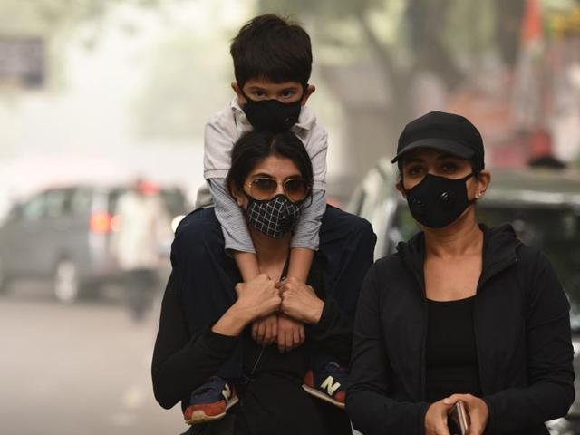 People wear pollution masks during a protest march at Jantar Mantar in New Delhi.