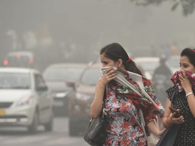 People wear masks to protect themselves from the toxic Delhi air, at Janpat Road in New Delhi on Sunday.