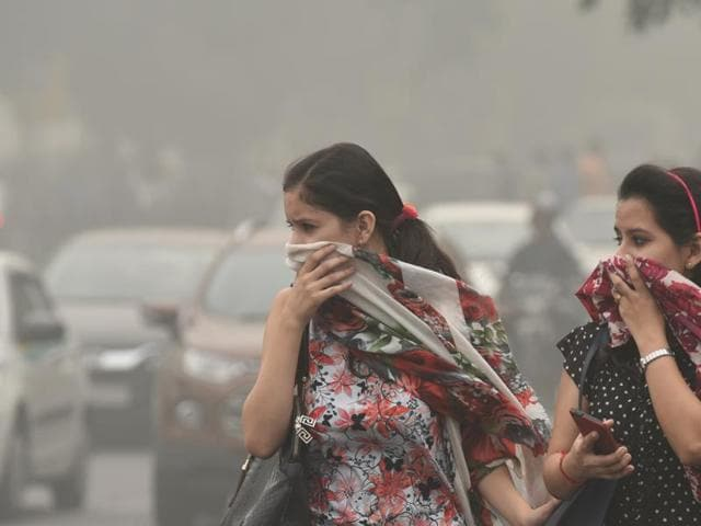 People cover their faces as a protective gear as pollution reached hazardous levels at Janpat Road in New Delhi.